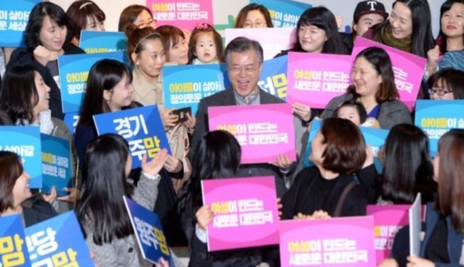 """Then-candidate Moon Jae-in poses with members of online """"mom cafes"""" nationwide in Hapjeong-dong, Seoul, on March 16, 2017. He holds a card in his hands, which reads: """"New Korea that is to be made by women."""" (Herald)"""