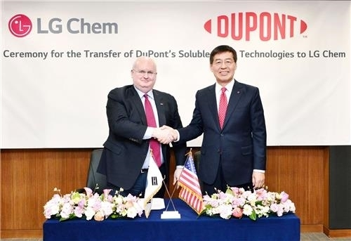 LG Chem Vice Chairman Shin Hak-cheol (right) shakes hand with DuPont Vice Chairman Marc Doyle during an acquisition ceremony held at the LG Chem headquarters in Seoul on Friday. (LG Chem)