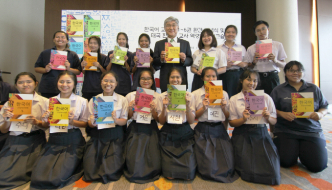 Thai students posing with their Korean language textbooks. (Yonhap)