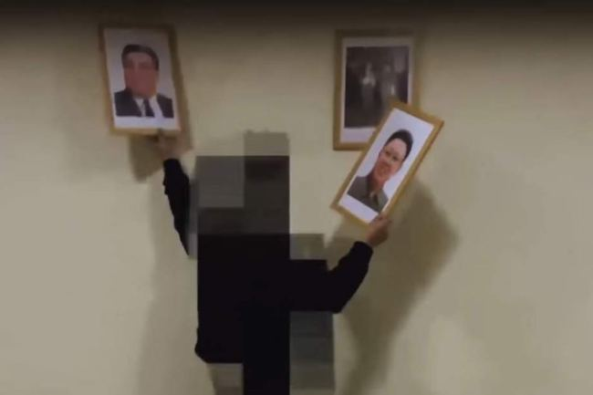 A screenshot of a video published on March 20 by Free Joseon shows a man removing portraits of North Korean leaders from the wall. (YouTube)
