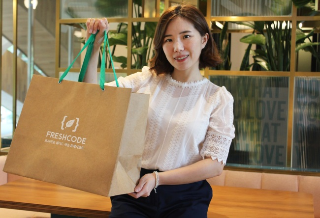 Regina Yoo, co-founder and CMO of Freshcode, poses with a bag of salads. (Freshcode)