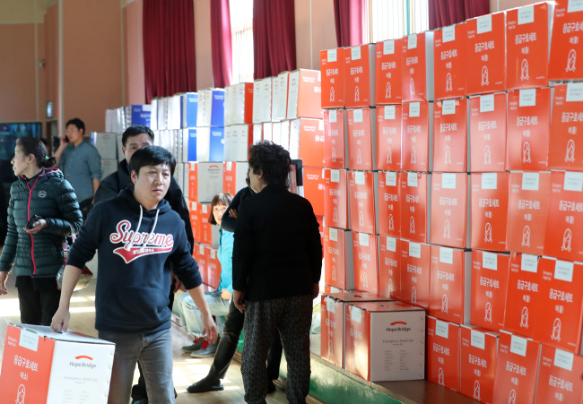 Volunteers distribute relief supplies to victims who lost their houses to fire. (Yonhap)