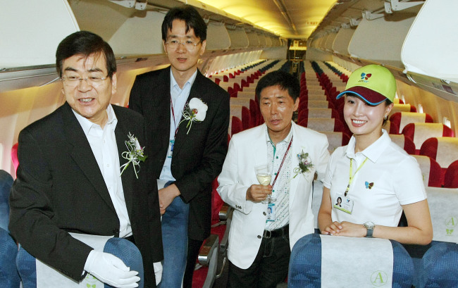 Late Hanjin Group Chairman Cho Yang-ho (first from left) and his son Cho Won-tae attend the inaugural flight ceremony of Jin Air, the group's budget carrier, in 2008. (Yonhap)