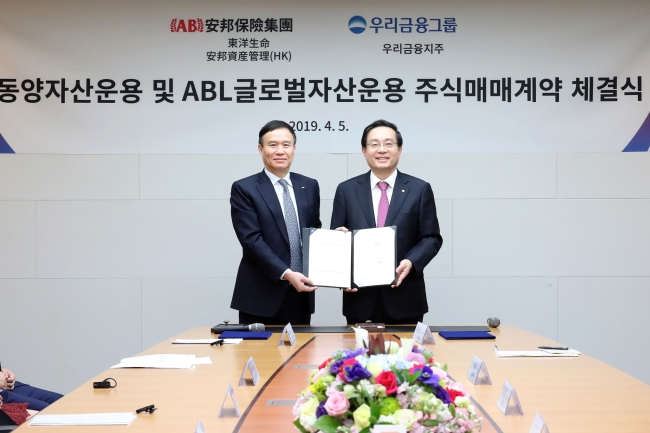 Woori Financial Group Chairman Sohn Tae-seung (right) and Tongyang Life CEO Luo Jianrong pose after signing a stock purchase agreement on Monday. (Woori Financial Group)