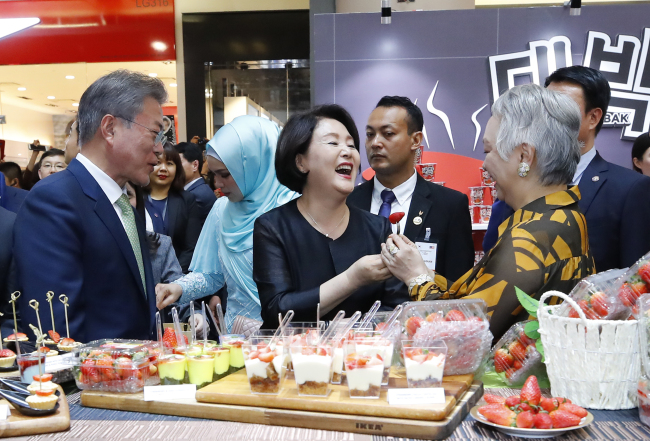 South Korean President Moon Jae-in (left) and first lady Kim Jung-sook (center) visit a booth to taste Korean strawberries at the K-Wave & Halal Show in Kuala Lumpur on March 12. (Yonhap)