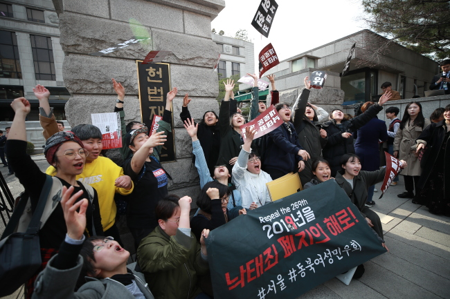 Pro-choice activists cheer in front of the Constituional Court, Thursday, following the ruling that ordered a revision of the current abortion ban. (Yonhap)
