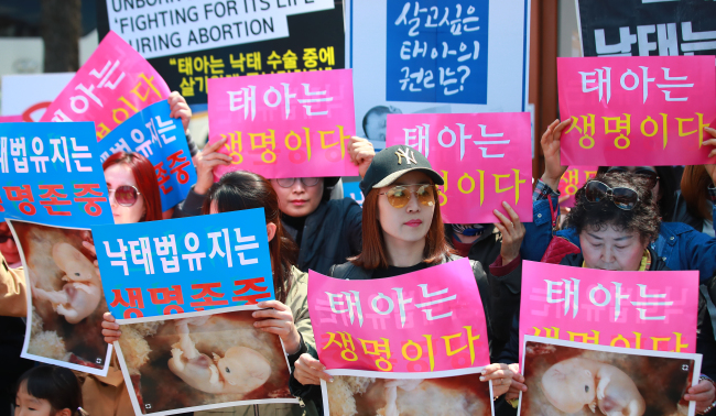 Anti-abortion activists hold placards reading