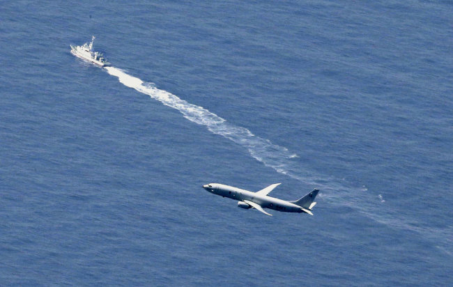 Japan Coast Guard vessel and a US military aircraft conduct rescue and search operations at the site where an Air Self-Defense Force's F-35A stealth fighter jet crashed during an exercise on Tuesday, off Aomori prefecture, Japan. (Reuters-Yonhap)
