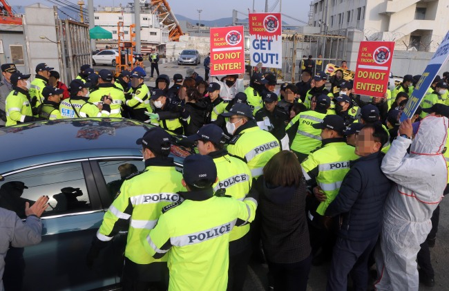 Residents opposing the US bio surveillance project JUPITR try to stop a vehicle from entering a military storage center for the United States Forces Korea, in Busan, March 25. (Yonhap)