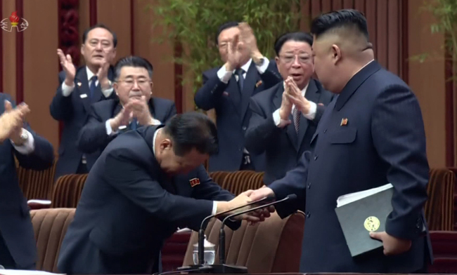 North Korean leader Kim Jong-un shakes hands with Choe Ryong-hae, who was named president of the Presidium of the Supreme People's Assembly at the first session of the country's rubber-stamp parliament Friday. The meeting was broadcast by state-run Korean Central Television on Saturday. (Yonhap)