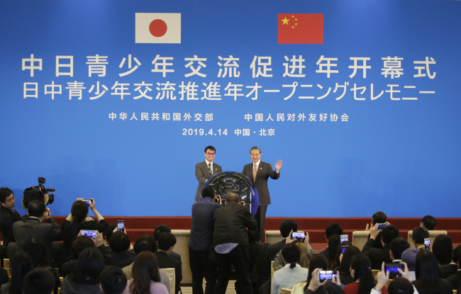 Japanese Foreign Minister Taro Kono (left) and China's Foreign Minister Wang Yi (right) attend an opening ceremony for the Japan-China year of youth exchange at Diaoyutai State Guesthouse in Beijing, China, Sunday. (AP-Yonhap)