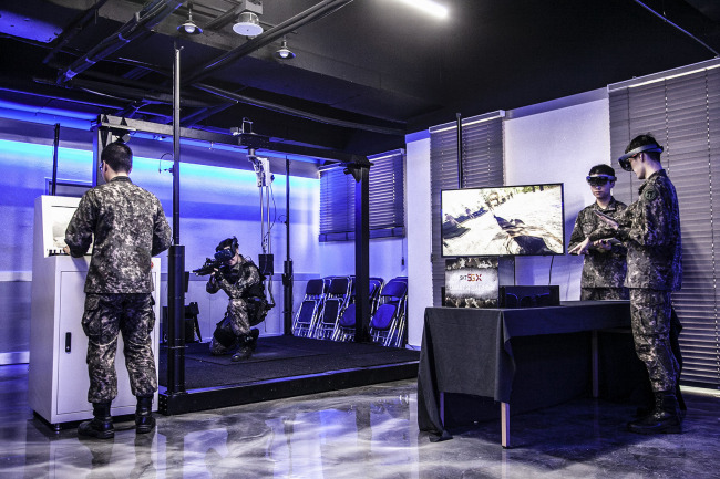 Army soldiers wearing augmented reality goggles monitor combat terrain in a hypothetical military campaign scenario. SKT
