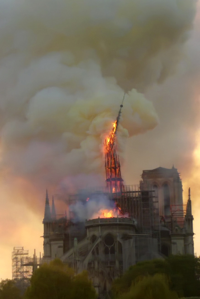 Flames and smoke rise as the spire of Notre Dame cathedral collapses in Paris, Monday, April 15, 2019. A catastrophic fire engulfed the upper reaches of Paris` soaring Notre Dame Cathedral as it was undergoing renovations Monday, threatening one of the greatest architectural treasures of the Western world as tourists and Parisians looked on aghast from the streets below. (AP)