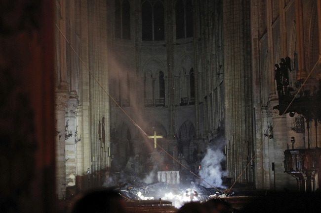Smoke is seen in the interior of Notre Dame cathedral in Paris, Monday, April 15, 2019. A catastrophic fire engulfed the upper reaches of Paris` soaring Notre Dame Cathedral as it was undergoing renovations Monday, threatening one of the greatest architectural treasures of the Western world as tourists and Parisians looked on aghast from the streets below. (AP)