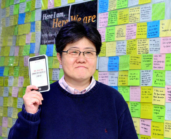 Cho Jin-kyeong holds up a Teens Up in front of a wall in her office full of messages of support for victims of underage prostitution. (Park Hyun-koo / The Korea Herald)