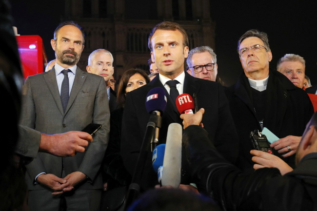 French President Emmanuel Macron speaks as Prime Minister Edouard Philippe and Archbishop of Paris, Michel Aupetit, stand near the Notre Dame Cathedral where a fire burns in Paris, France, 15 April 2019. (EPA=Yonhap)