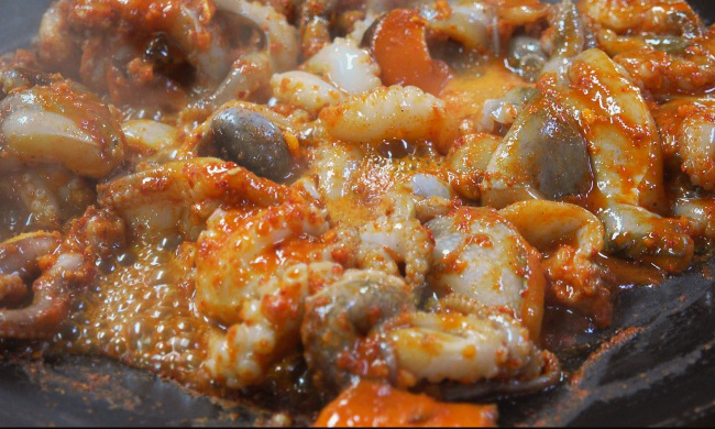 Jjukkumi, heavily doused with gochujang, is stir-fried in a large, shallow pan. (Lee So-jung/The Korea Herald)
