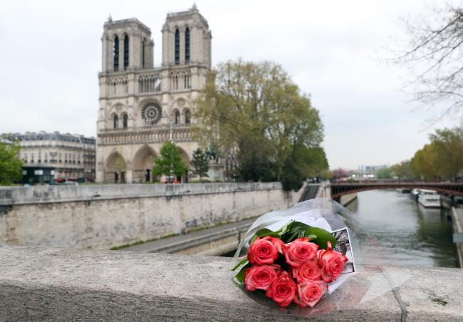 Flowers are laid before Notre Dame Cathedral after a giant fire was put down in Paris 16 April 2019. French President Emmanuel Macron vowed to rebuild the 13th century building that welcomes tens of millions of worshippers and tourists per year. (Yonhap)