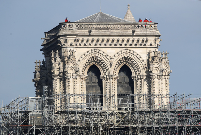 French President Emmanuel Macron vowed to rebuild the 13th century building that welcomes tens of millions of worshippers and tourists per year. (Yonhap)