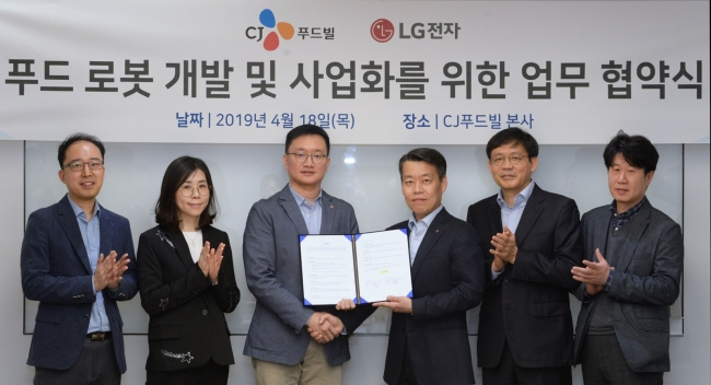 Officials at LG Electronics and CJ Foodville hold a MOU agreement at CJ's head office in central Seoul on Thursday. (LG Electronics)