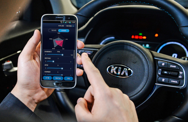 A driver tests Hyundai Motor's mobile EV tune-up technology on a smartphone. (Hyundai Motor)