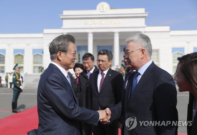 South Korean President Moon Jae-in (L) shakes hands with Kazakh officials at Nur-Sultan International Airport in Nur-Sultan, Kazakhstan, on April 23, 2019, prior to his departure for home, ending a weeklong Central Asia tour that also took him to Turkmenistan and Uzbekistan. (Yonhap)