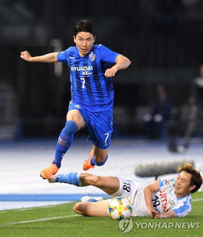 In this AFP photo, Kim In-sung of Ulsan Hyundai FC jumps over Manabu Saito of Kawasaki Frontale during their Group H match in the Asian Football Confederation Champions League at Todoroki Athletics Stadium in Kawasaki, Japan, on April 23, 2019. (Yonhap)