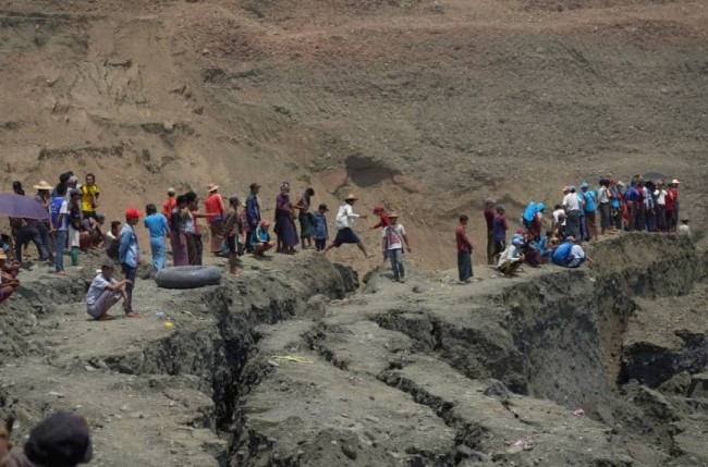 Local people look around a jade mine where the mud dam collapsed, in Hpakant, Myanmar on Tuesday. (REUTERS)
