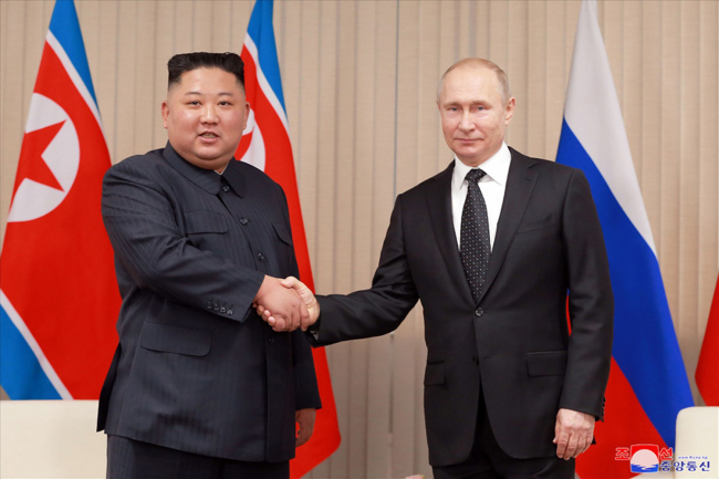 North Korean leader Kim Jong-un (left) and Russian President Vladimir Putin shake hands Thursday in Vladivostok in a photo released by North Korean state media. (Yonhap)