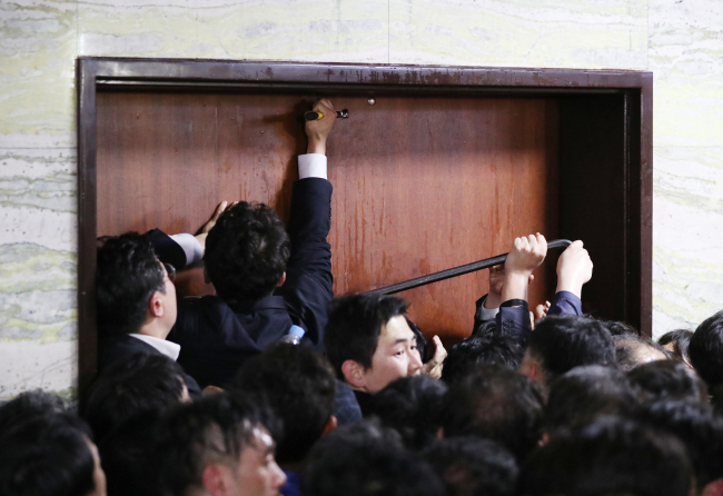 Ruling Democratic Party of Korea officials and National Assembly officials attempt to enter the bill registration office on the seventh floor of the National Assembly, occupied by the Liberty Korea Party, using hammers and other instruments, to submit a bill on adjusting investigative authority on Friday. (Yonhap)