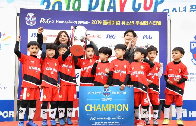 A youth futsal team holds up the championship cup after winning first place. (Homeplus)
