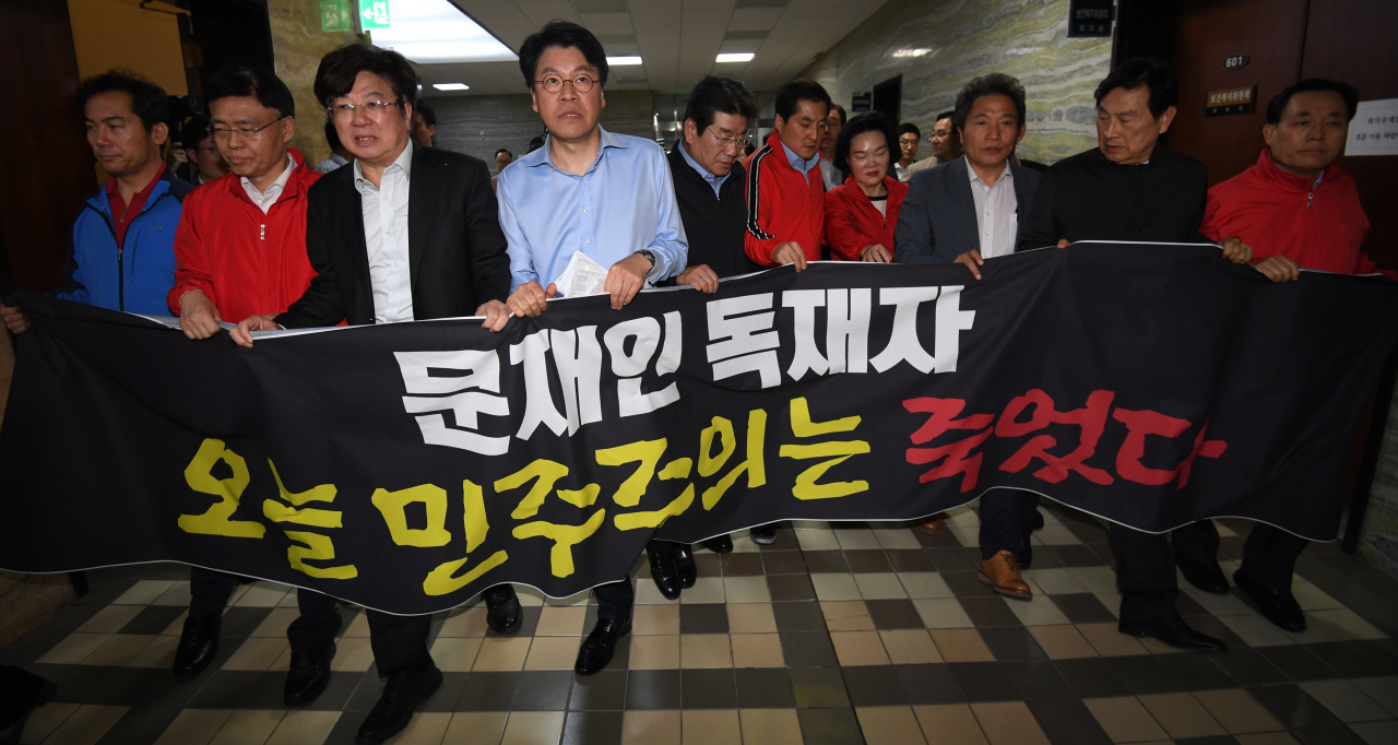 Liberty Korea Party lawmakers walk along a corridor at the National Assembly holding a banner that reads