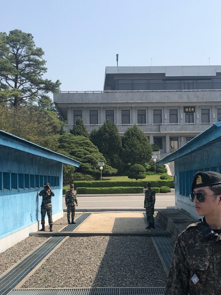 North Korean officers stand on the northern side of the JSA behind the Military Demarcation Line to check the southern side, with one of them taking pictures on Wednesday. (Jo He-rim/The Korea Herald)