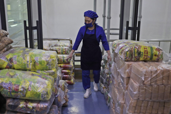 In this March 13, 2019, photo, a worker walks among stacks of food at Kumkhop Trading Co. food factory in Pyongyang, North Korea. North Korean factories are filling city store shelves with ever better and fancier snack foods and sugary drinks, while government officials and international aid organizations warn the nation could be on the verge of a major food crisis. (AP Photo/Dita Alangkara)