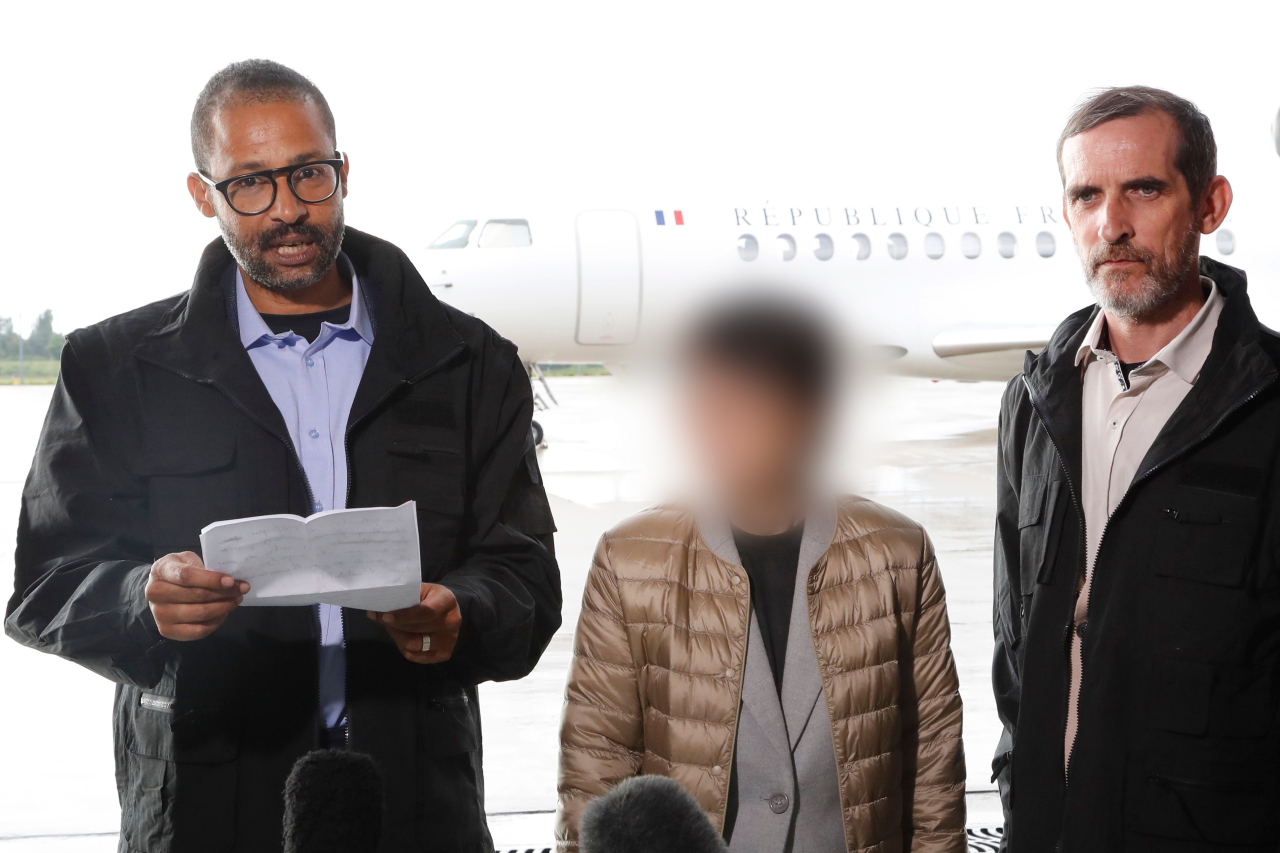 Korean woman (center) and French nationals rescued from militants speak to the media at a French military airbase on Saturday. Yonhap