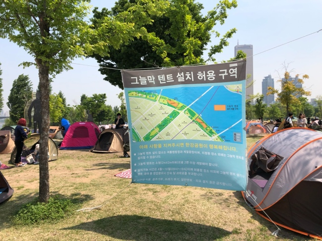 A placard is hung between trees to inform the public of the area designated as a tent zone in Yeouido Hangang Park in southwestern Seoul on Saturday afternoon. (Ock Hyun-ju/The Korea Herald)