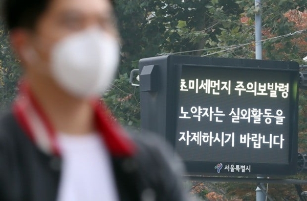 A masked man stands in front of a screen displaying an ultrafine dust emergency warning. (Yonhap)
