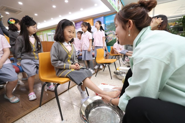 A teacher at an elementary school in Daegu dries a student's foot after a foot bath Wednesday during a Teachers' Day event. (Yonhap)