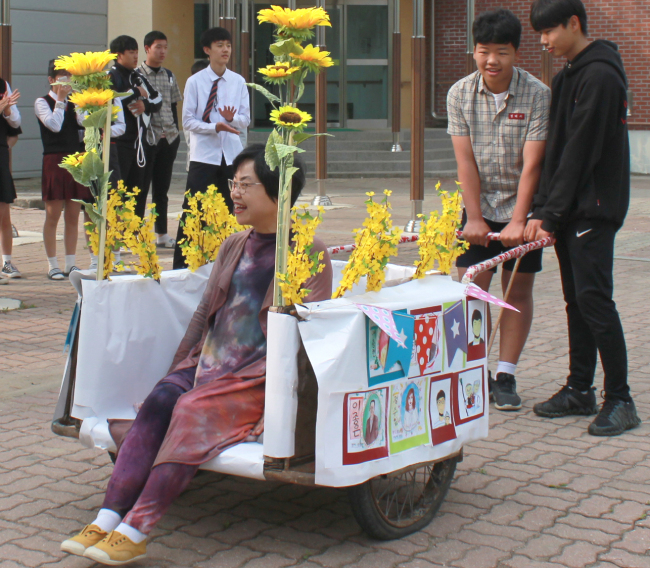 Middle school students in Cheongju, North Chungcheong Province, carry their teacher on a wagon decorated with flowers on Wednesday. (Miwon Middle School/Yonhap)
