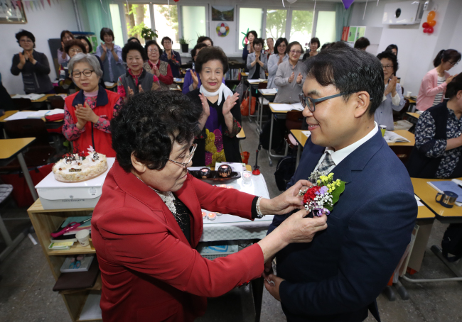 An elderly woman and lifelong learner attaches a corsage to her teacher's jacket Wednesday in Mapo-gu, Seoul. (Yonhap)