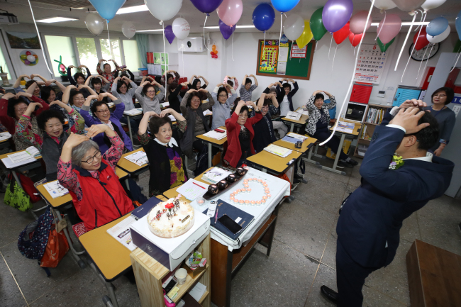 Lifelong learners studying in Seoul make hearts over their heads during a Teachers' Day event on Wednesday. (Yonhap)