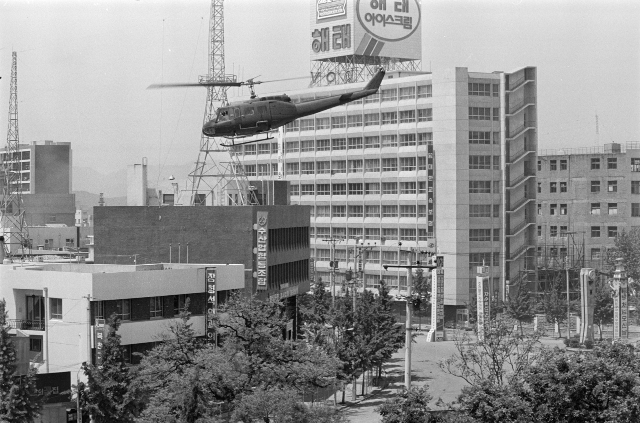 A helicopter hovers in front of the 10-story Jeon Il building located across the street from the former South Jeolla Provincial Government building during the Gwangju Democratic Uprising in May 1980. (The May 18 Memorial Foundation)