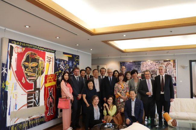"POSING WITH BASQUIAT -- Choi Jung-wha (third from left, second row), head of the Corea Image Communication Institute, Kim Young-ho (fourth from left, second row), Ilshin Spinning chairman, and H.E. Federico Failla (fifth from left, second row), Italian ambassador to Korea, pose for photos next to artist Jean-Michel Basquiat's painting ""TBT,"" along with other guests at ""Korea CQ, 5.4 Club,"" an event hosted by CICI at the Ilshin Spinning headquarters in Yeouido, Seoul, Tuesday. (CICI)"