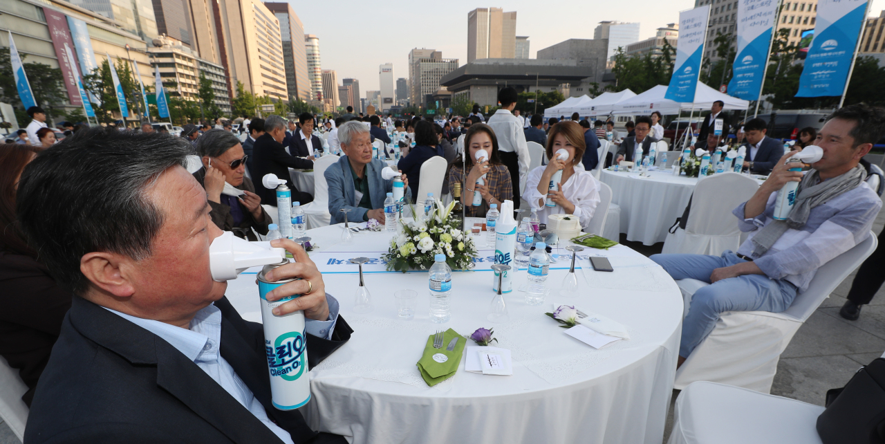 "Participants try inhaling from portable oxygen tanks at the ""Dining in Find Dust"" event in Gwanghwamun Square, Seoul, Tuesday. (Yonhap)"