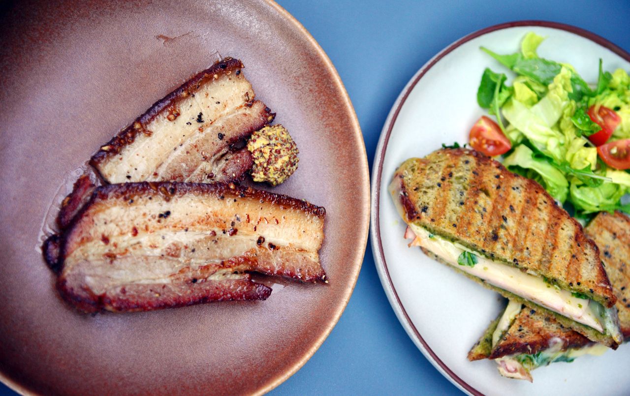 Jungsik Cafe's from-scratch attitude shines through with their housemade bacon (left) -- which is cured for a week with salt and maple syrup, smoked and seasoned with whole peppercorns, fennel seeds and coriander seeds -- and their panini -- crafted from housemade sesame campagne, housemade basil pesto, smoked pork loin ham, Comte cheese and rucola (Photo credit: Park Hyun-koo/The Korea Herald)