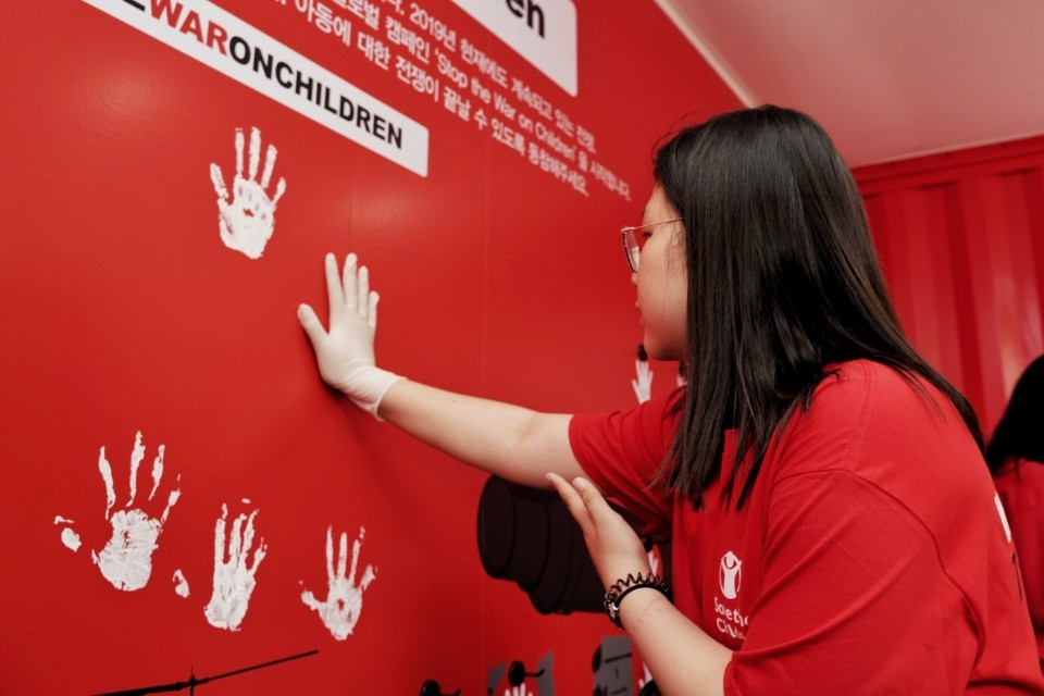 "A participant makes handprints on a wall as part of the ""Stop the War on Children"" campaign. (Save the Children)"