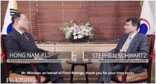 Hong Nam-ki (left), the minister of economy and finance, holds an interview with global credit appraiser Fitch Ratings in this still from a video posted on its website.