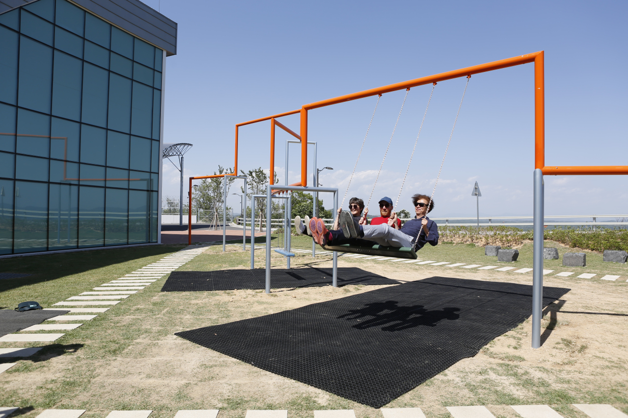 From left, Kim Sun-jung, president of the Gwangju Biennale Foundation, Jakob Fenger of Superflex and professor Zoh Kyung-Jin of Real DMZ Project are riding on the swing-set designed by Danish artist group Superflex on Tuesday at Dora obsevatory in Paju, Gyeonggi Province. (Real DMZ Project)