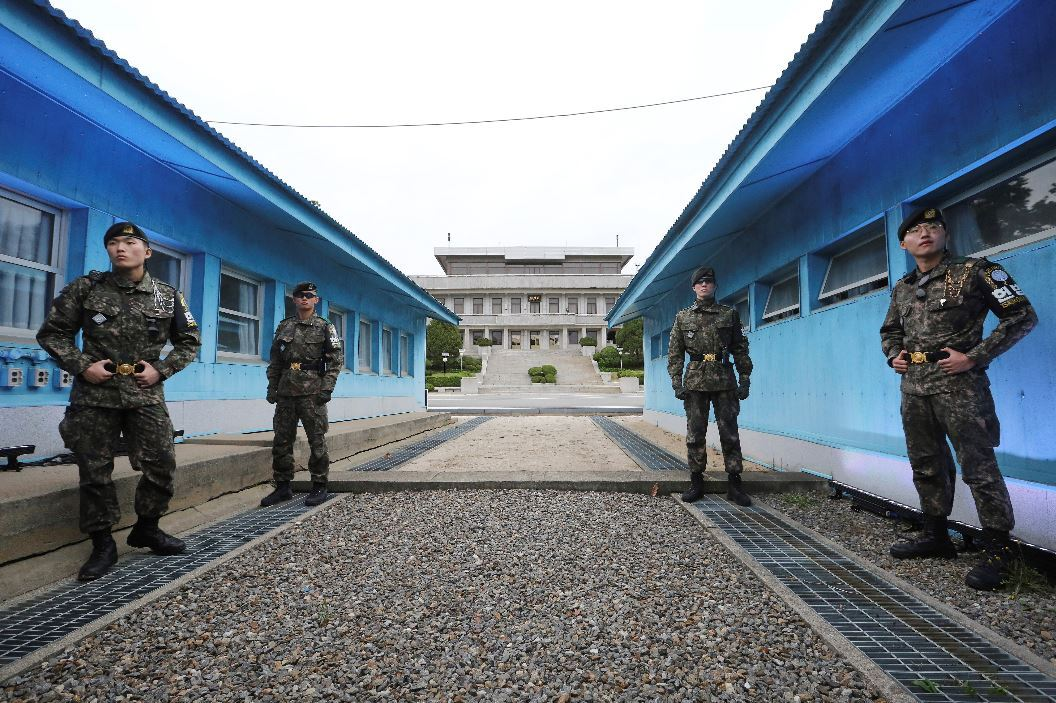"South Korean soldiers stand guard before North Korea's Panmungak (rear, center) and the Military Demarcation Line separating two Koreas in Joint Security Area. Tourists are allowed to visit the ""Truce Village"" of Panmunjom in JSA since May 1, after the two sides removed landmines and weapons out of guard towers to ease tensions. (Yonhap)"