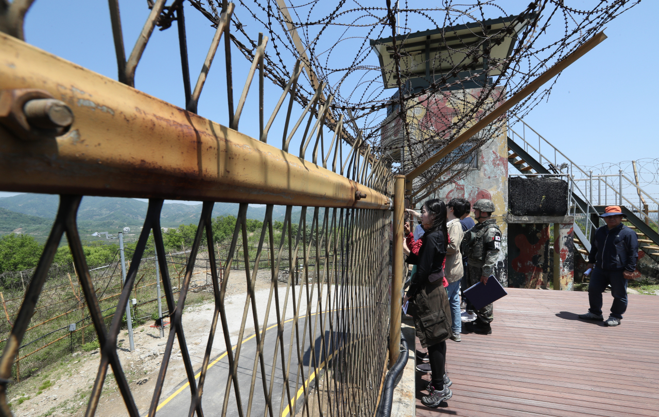 Visitors look through barbed fences near the Demilitarized Zone in Cheorwon County, Gangwon Province, on one of the three DMZ Peace Trails planned by the South Korean government. (Joint Press Corps)